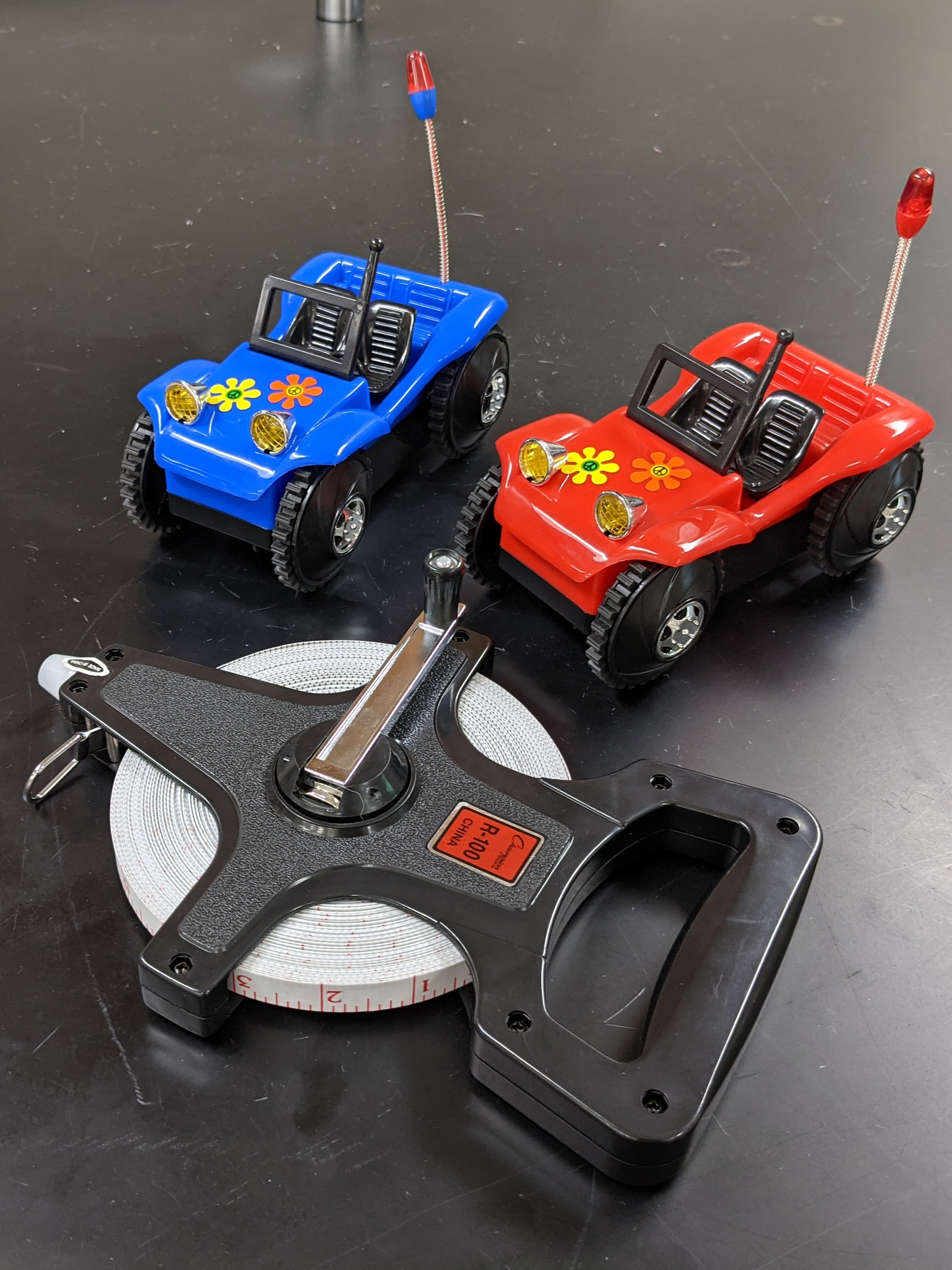 A blue tumble buggy and a red tumble buggy sitting next to a measuring tape